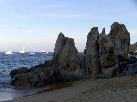 A rock at the beach, with some boats in the background